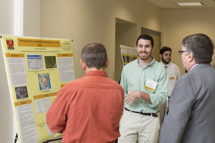 Photo of Birla Carbon Scholar, Ian Duncan, presenting his research poster at the 2017 Birla Carbon Scholars Symposium on August 29, 2017