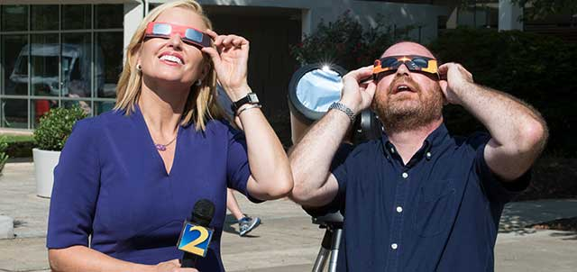 Linda Stouffer, WSB-TV anchor and reporter, takes a break from an interview with Associate Professor of Physics David Joffe on the Marietta Campus to check out the new solar eclipse glasses that students will use on Aug. 21 to safely view the eclipse; Link to article on News at KSU website